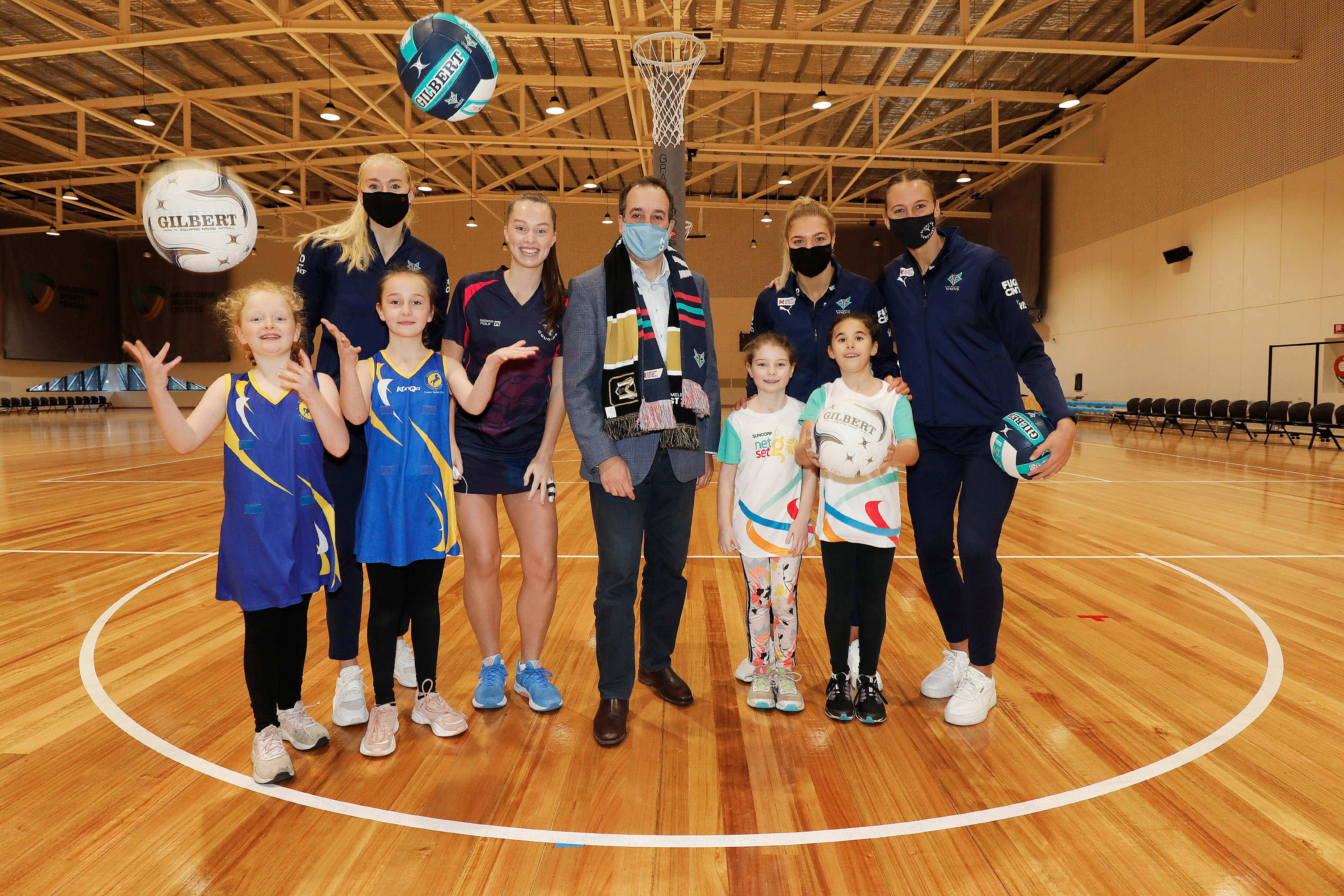 Netballers standing with children who have thrown two netballs in the air