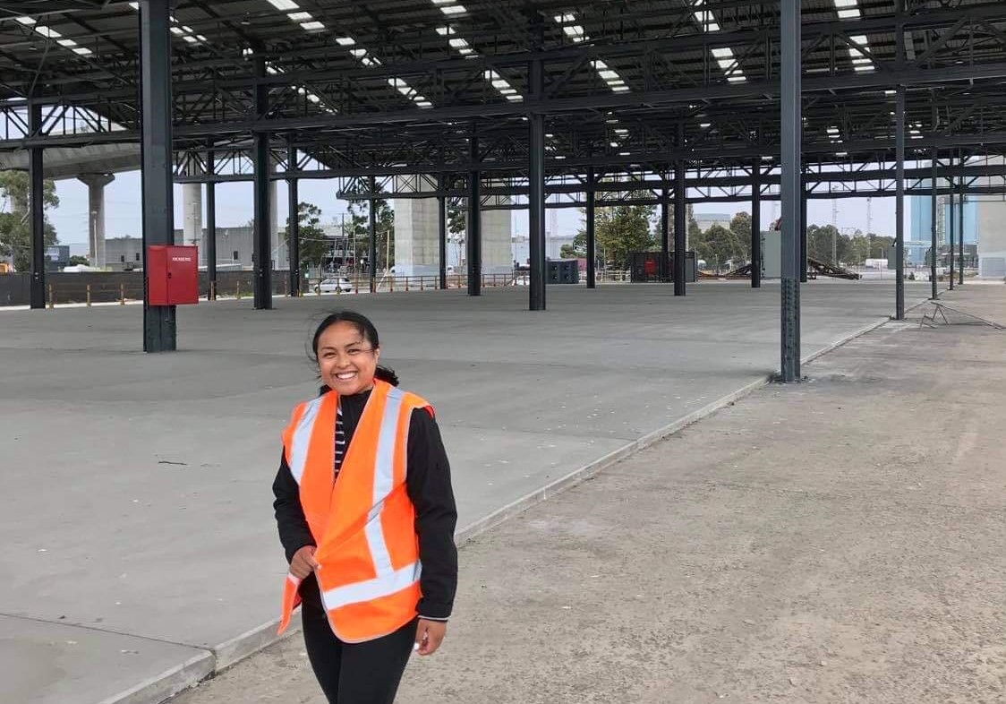 Shania Nagy a young woman wearing an orange hi-vis vest smiling at Bolte Precinct West