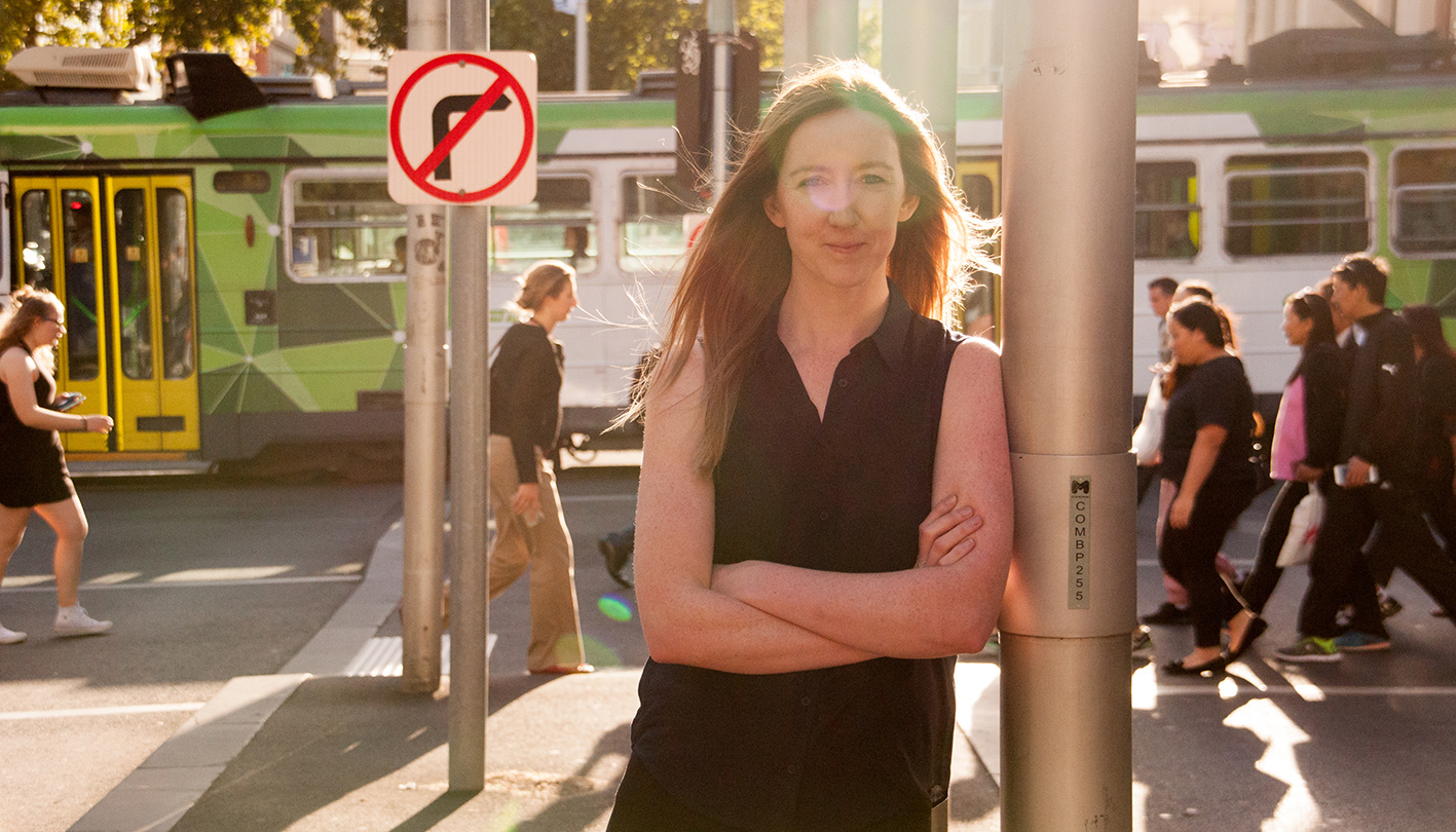 A woman in a black top standing with her arms crossed leaning against a pole