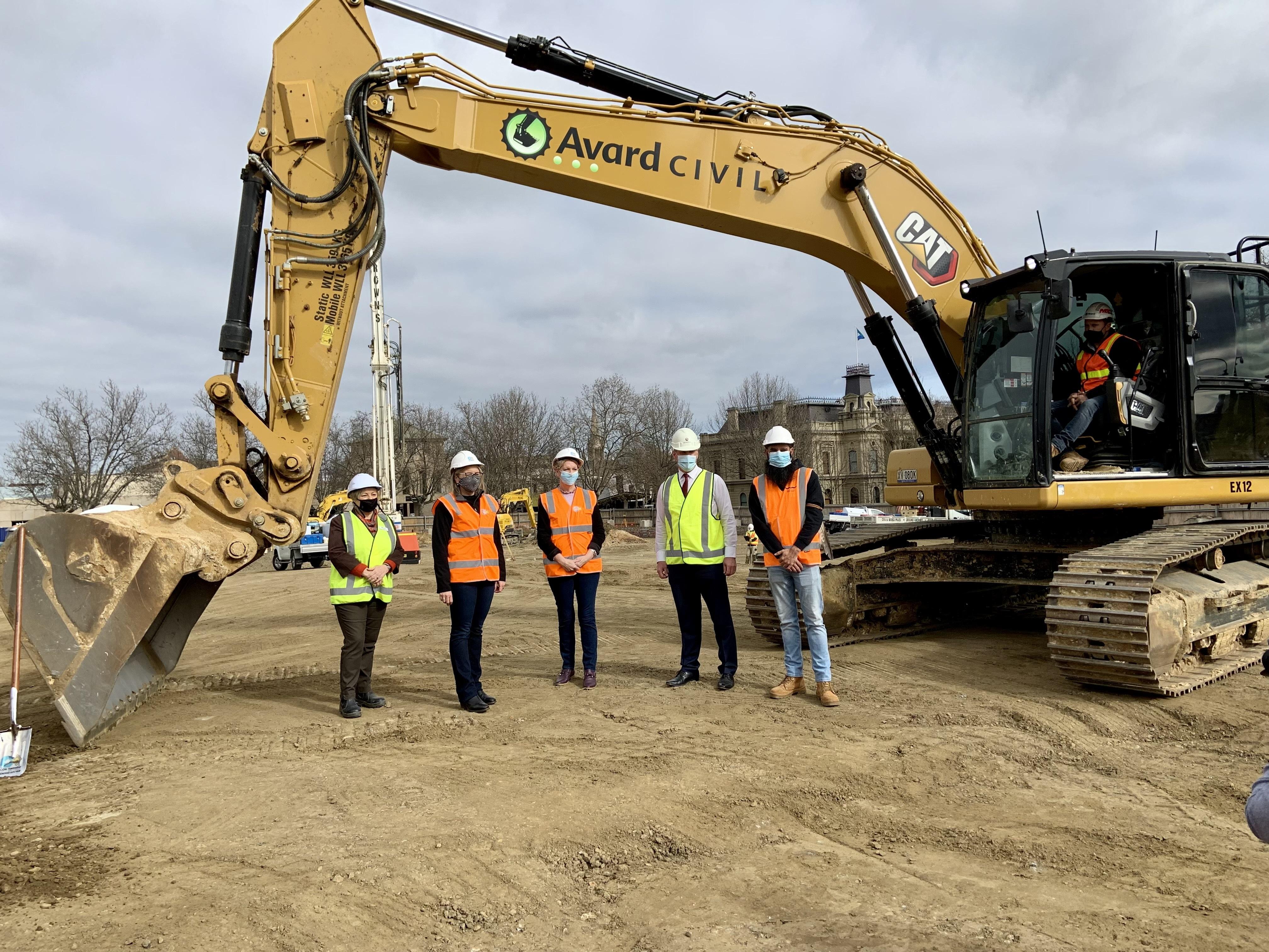 Five people in high vis vests standing in front of excavator